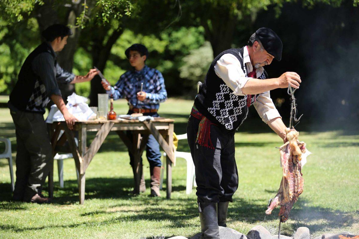 A gaucho prepares meat on an asado