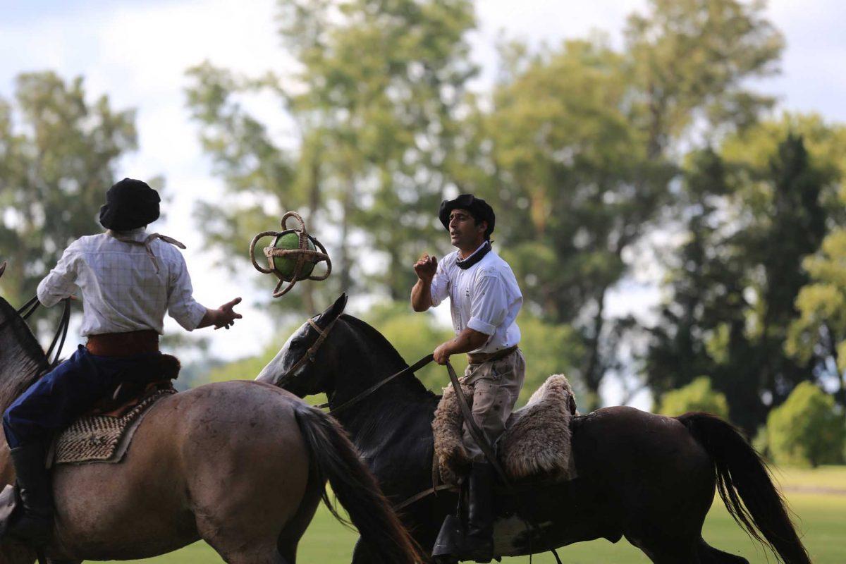 Two gauchos on horseback pass a ball